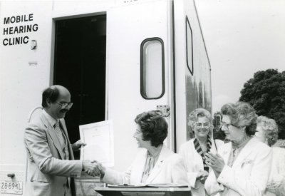 Mike Harcourt and Miriam Warren shaking hands, with three other unidentified women in front of the mobile hearing clinic, (L.16462).